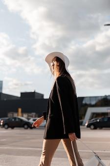 黒のジャケットに帽子とサングラスをかけた美しい女性が日没時に街を歩く
