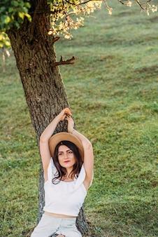 木の近くの帽子を持つ美しい女性