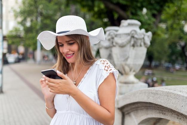 휴대 전화를 사용 하여 모자와 아름 다운 여자