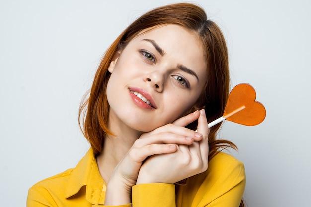 Красивая женщина с леденцом на палочке сердца