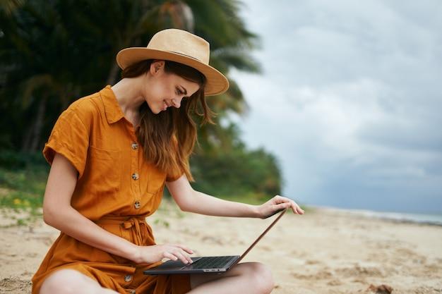 Красивая женщина с ноутбуком сидит на песке и работает
