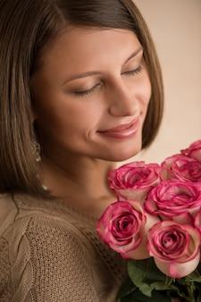 향기로운 핑크 장미 냄새가 그녀의 팔에 꽃의 큰 꽃다발과 함께 아름 다운 여자