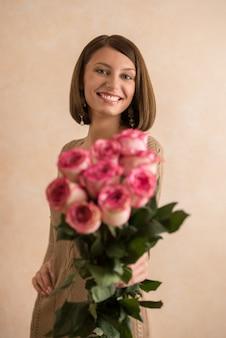 그녀의 팔에 꽃의 큰 꽃다발과 함께 아름 다운 여자