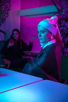 モダンなカフェで昼食をとる真珠の耳飾りの美しい女性