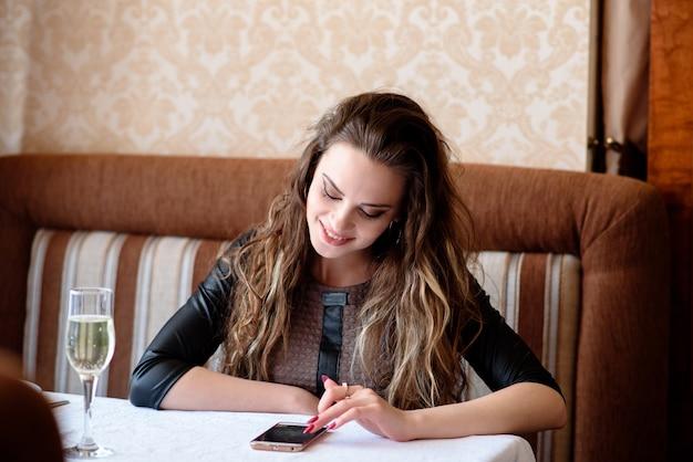 Красивая женщина с телефоном за столиком в ресторане