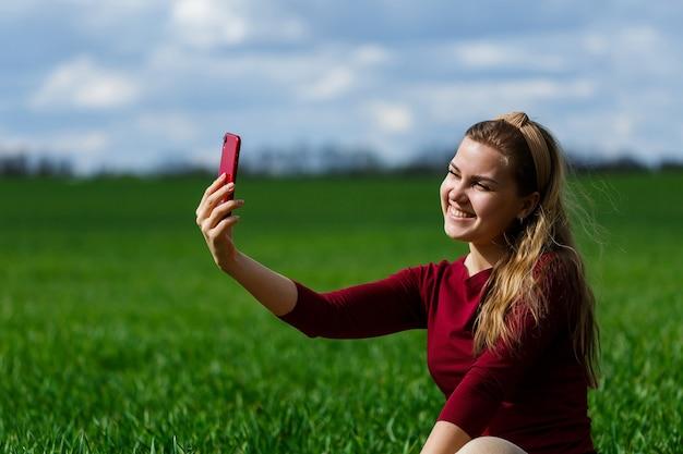 彼女の手に携帯電話を持つ美しい女性は草の上に座っています。女の子は携帯電話のカメラで自分を見て、自分撮り写真を撮ります。彼女は微笑んで暖かい日を楽しんでいます。スマートフォンのコンセプト写真