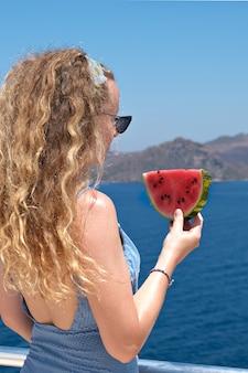 Красивая женщина с кусочком арбуза в купальнике ест красный спелый арбуз с лета отдыха с видом на море.