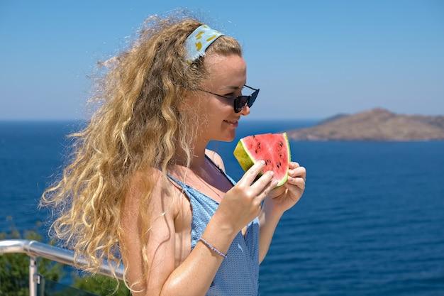 海の景色の休日の夏と赤い熟したスイカのスライスを食べる水着を着てスイカのスライスを持つ美しい女性。