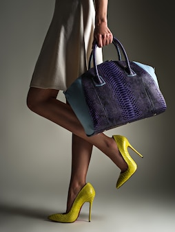 黄色いハイヒールでスリムな脚を持つ美しい女性。ファッショナブルな女の子はスタイリッシュな青いバッグを保持しています。グラマースタイリッシュなコンセプト。アート。女性は買い物の後に歩きます。認識できない女性。