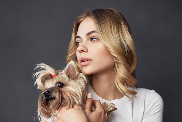 トリミングされたビューをポーズする小さな犬のメイクアップを持つ美しい女性