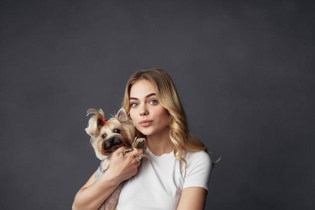 暗い背景をポーズする小さな犬の化粧と美しい女性