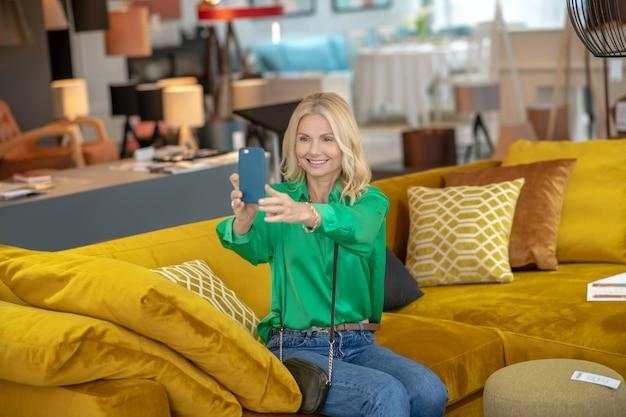 그녀의 어깨 너머로 작은 핸드백과 아름 다운 여자, 가구 살롱에서 노란색 소파에 앉아 행복 한 selfie를 복용.