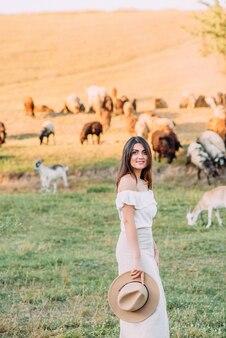 自然の中で白いブラウスを持つ美しい女性
