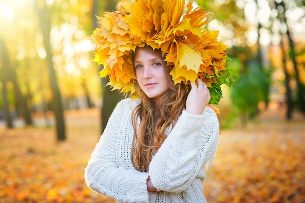 公園で黄色の葉の花輪を持つ美しい女性。
