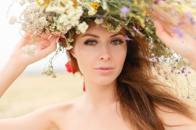 Красивая женщина с венком на голове сидит в поле в цветах. понятие красоты, свободной жизни и естественности