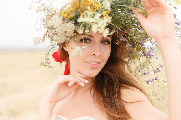 花のフィールドに座っている彼女の頭に花輪を持つ美しい女性。美しさ、自由な生活、自然の概念