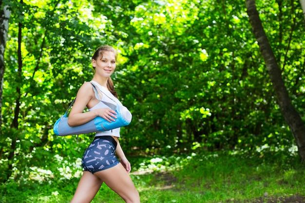 Красивая женщина с коврик для йоги на открытом воздухе.