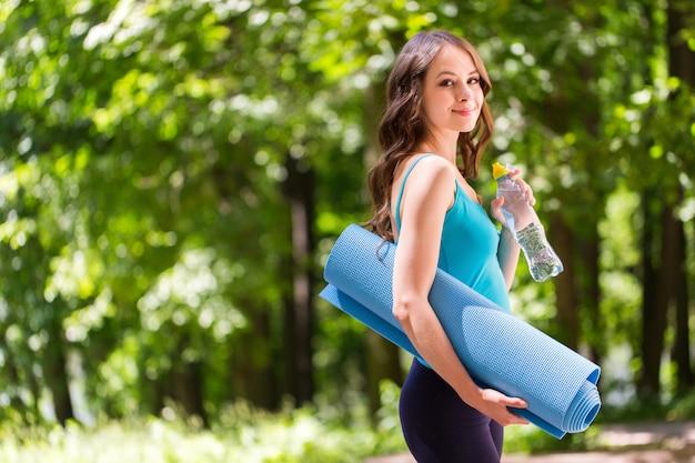 Красивая женщина с ковриком для йоги на открытом воздухе