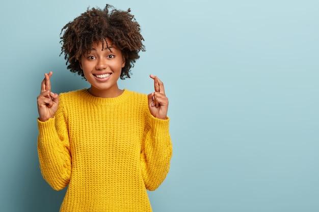 Bella donna con un afro che propone in un maglione rosa