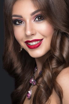 Beautiful woman with arabic make-up, red lips and curls
