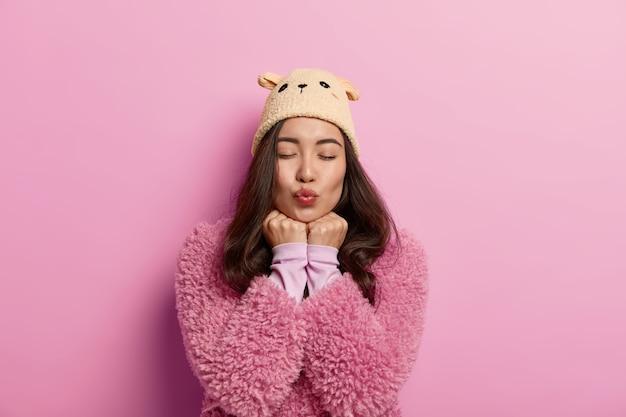 아시아 외모를 가진 아름다운 여인은 입술을 접고, 닫힌 눈으로 열정적 인 키스를 기다립니다. 손을 턱 아래에 유지하고 세련된 겨울 옷을 입습니다.
