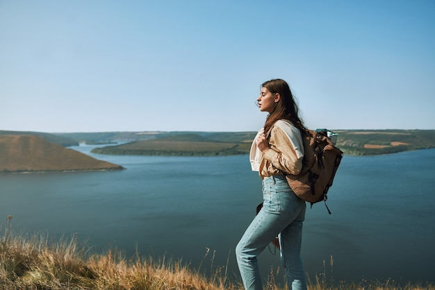 Beautiful woman with backpack on hill near dniester river