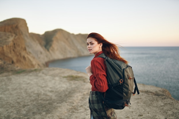 Beautiful woman with a backpack in the mountains red sweater model hairstyle ocean sea