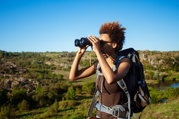 Beautiful woman with backpack smiling, holding binoculars