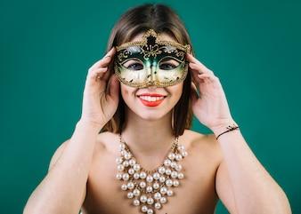 緑の背景にビーズのネックレスとカーニバルマスクを持つ美しい女性