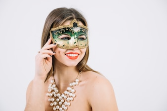 Beautiful woman with beads necklace and carnival mask on white backdrop