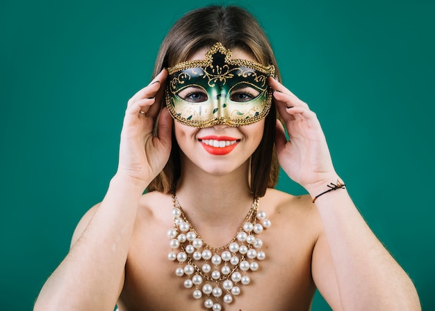 Beautiful woman with beads necklace and carnival mask on green backdrop