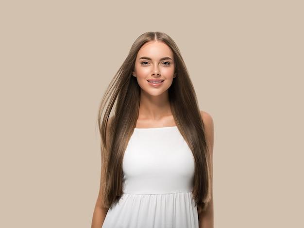 Красивая женщина с красивыми длинными гладкими развевающимися волосами в белом платье на цветном фоне