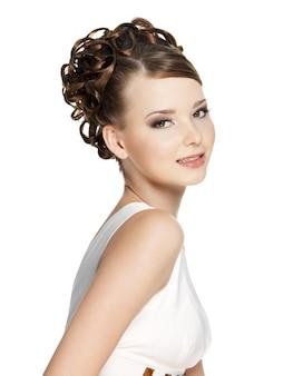 Bella donna con l'acconciatura di bellezza su bianco