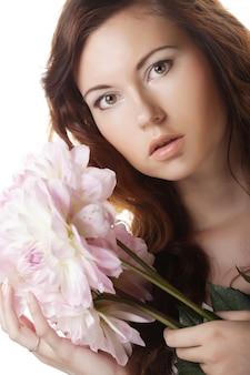 大きなピンクの花を持つ美しい女性