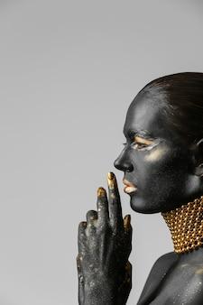 Красивая женщина с черной и золотой краской на теле