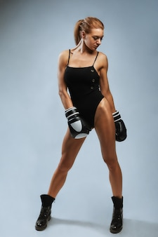 Beautiful woman with black boxing gloves on a gray background copy space sport banner