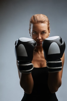 Beautiful woman with black boxing gloves on a gray background