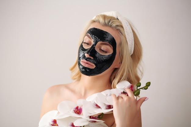 彼女の顔に黒のクリーニング黒チャコールマスクを持つ美しい女性。