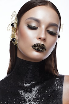 Beautiful woman with black creative art make-up and gold accessories