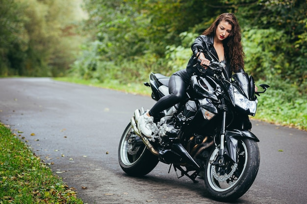 Beautiful woman, with black curly hair, in a black leather jacket, sitting on a sports motorcycle