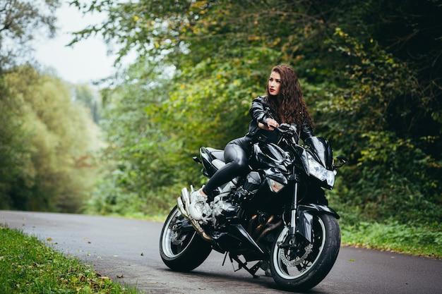 スポーツバイクに座って、黒い革のジャケットを着た黒い巻き毛の美しい女性