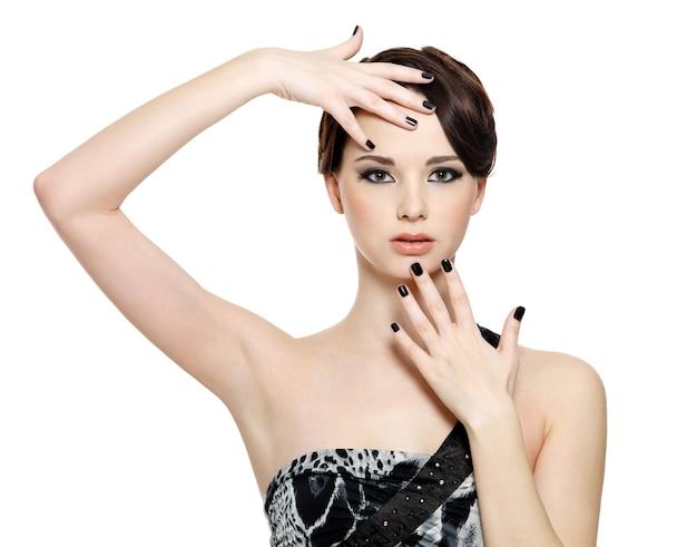 明るい魅力で顔の近くに黒い爪を持つ美しい女性