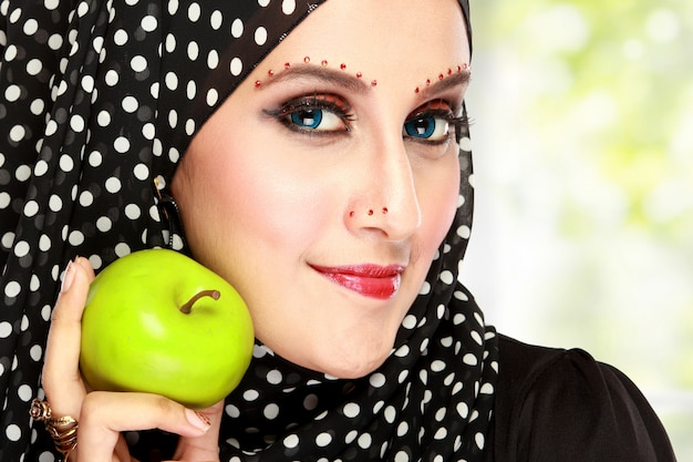 Beautiful woman with black scarf holding green apple