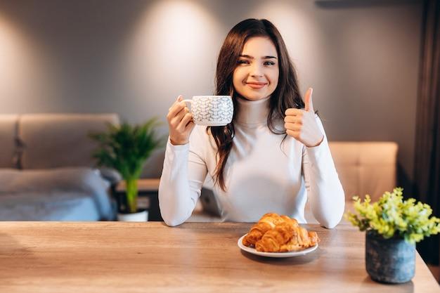朝食時にコーヒーを飲む黒い光沢のある髪の美しい女性。クロワッサンを食べて、朝のお茶を楽しんでいるかわいいブルネットの少女の屋内の肖像画。