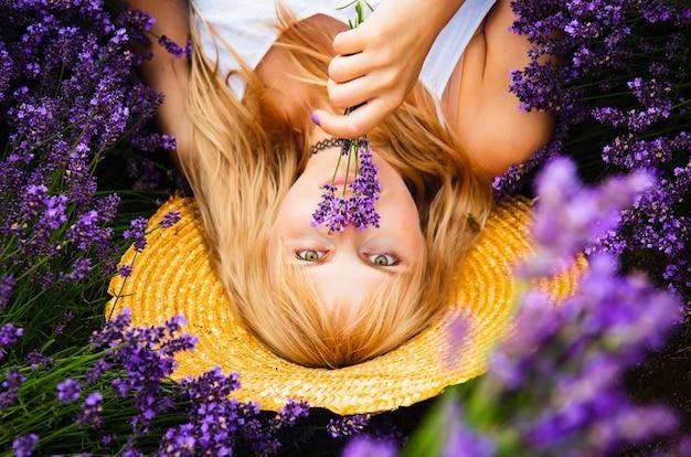 Красивая женщина со светлыми волосами лежит в поле цветов лаванды