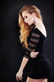검은 드레스를 입고 금발 곱슬 헤어스타일으로 아름 다운 여자입니다. 프로필