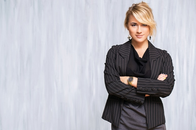Beautiful woman with blonde hair and black suit