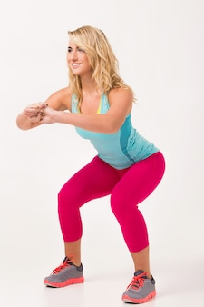 Beautiful woman with blonde hair and in training clothes is working out over a white background