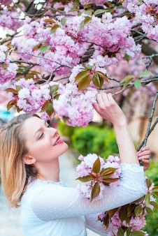 Beautiful woman with blooming sakura tree and sunny day. daisy flower, flowering daisy flowers in meadow.