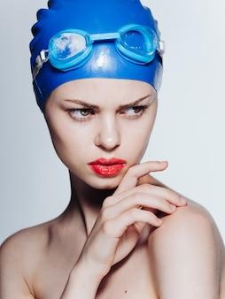 그녀의 머리와 붉은 입술에 파란색 안경을 가진 아름 다운 여자는 어깨를 드러냈다